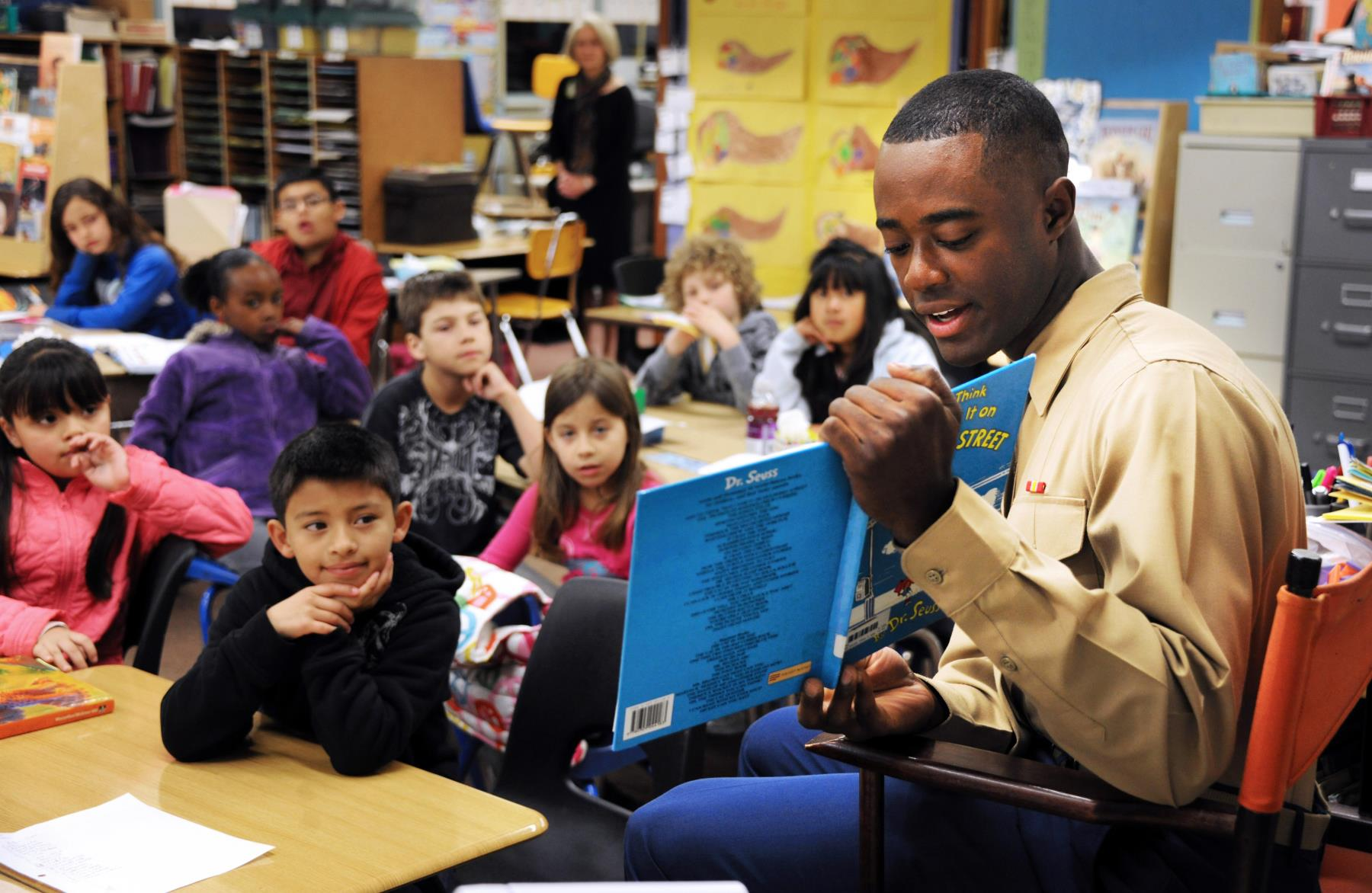 a marine reading a book to children in a classroom