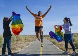 Runner on road jumping between two spectators waving rainbow flags