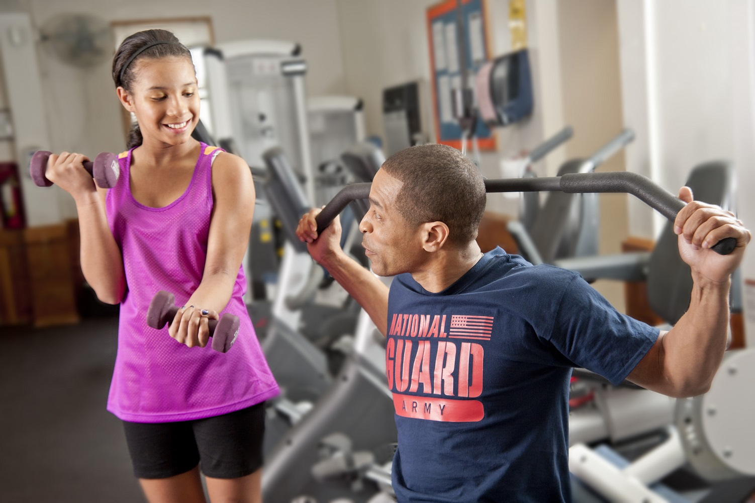 Teen girl exercising with weights with her father who is also exercising with weights